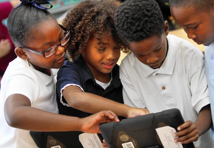 STUDENTS explore the possibilities with their new LAUSD-provided IPads. A new report says the district inadequately planned the distribution of an iPad to each student.