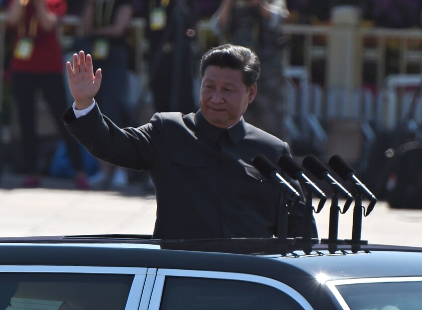 Chinese President Xi Jinping waves as he reviews troops from a car during a military parade at Tiananmen Square in Beijing.