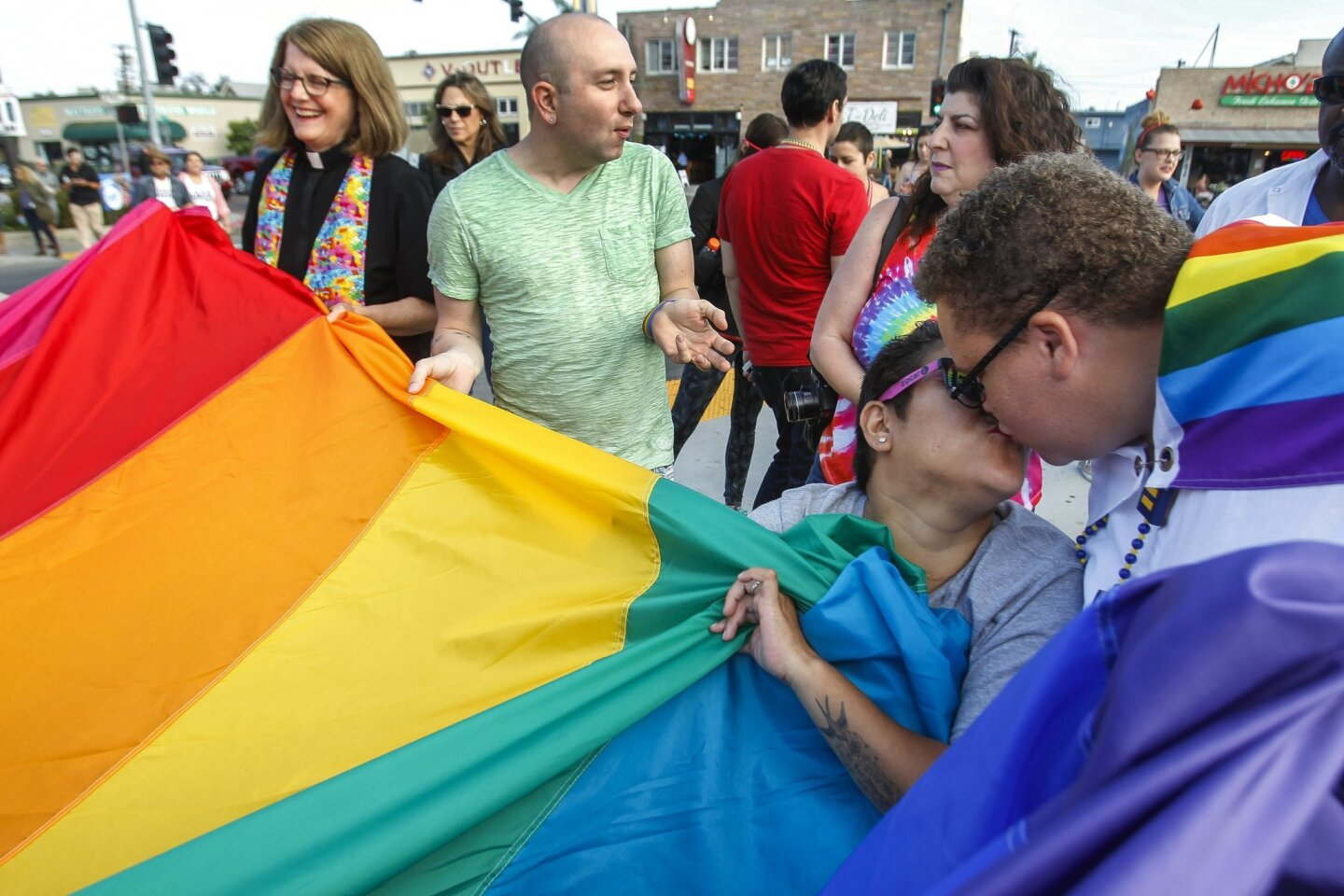 Jamie Gardner, right, kisses  Gabby Gardner, who are married to each other, as Gabby holds on to the on the Pride Constellation flag as people celebrate the marriage equality ruling by the Supreme Court in Hillcrest.