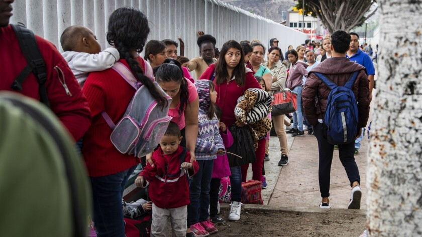 TIJUANA, MEXICO - JUNE 20, 2018: Asylum- seeking immigrants line up at a border fence after their n