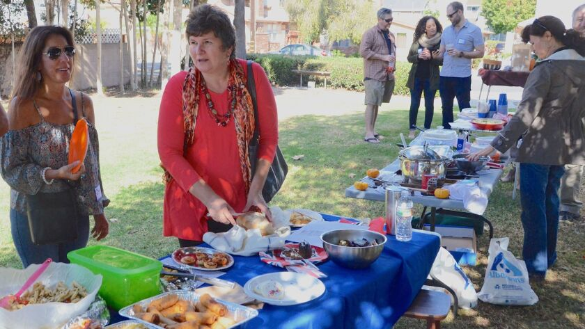 Lisa George, left, and Rodica Ioba meet during a potluck picnic at Heller Park in Costa Mesa organized to bring together people from their neighborhood who are in the Nextdoor social network.