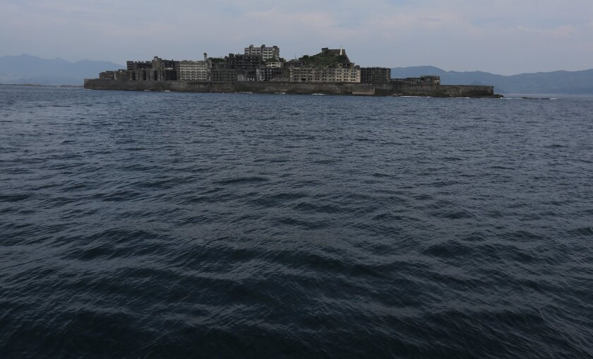 """In this June 29, 2015 photo,  Hashima Island, commonly known as Gunkanjima, which mean """"Battleship Island,"""" is seen off Nagasaki, Nagasaki Prefecture, southern Japan. Japanese officials expressed elation Monday, July 6, 2015, over the U.N. cultural body's approval of world heritage status for 23 hi"""