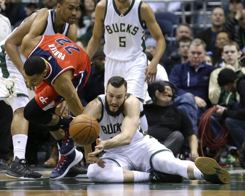 Milwaukee Bucks' Miles Plumlee, bottom, and Washington Wizards' Otto Porter Jr. (22) fight for a loose ball during the first half of an NBA basketball game Thursday, Feb. 11, 2016, in Milwaukee. (AP Photo/Aaron Gash)