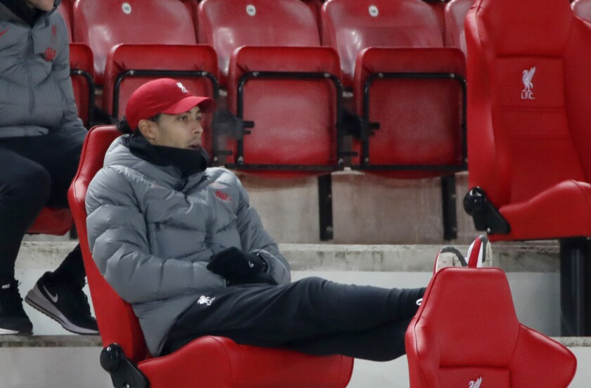 """FILE - In this file photo dated Sunday, Dec. 6, 2020, Liverpool's Virgil van Dijk watches from the stands during the English Premier League soccer match against Wolverhampton Wanderers at Anfield Stadium, Liverpool, England. Liverpool manager Jurgen Klopp on Saturday May 1, 2021, dampened hopes of Virgil van Dijk playing for the Netherlands at the European Championship, saying it will be """"very, very tight"""" whether the defender can be fit in time because he's not close to resuming full training. (Clive Brunskill/Pool FILE via AP)"""