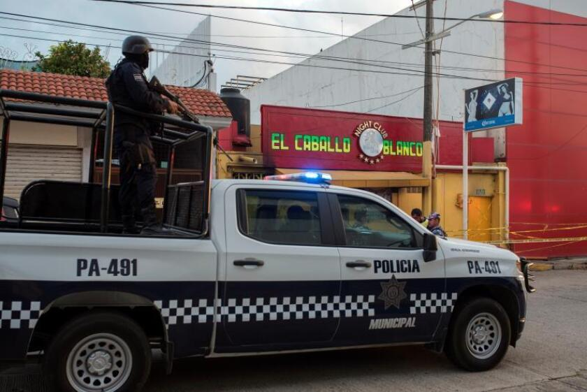 Agentes de la policía pasan este miércoles frente al bar El Caballo Blanco, atacado ayer por un grupo armado, en Coatzacoalcos, en el estado de Veracruz (México). EFE/ Ángel Hernández