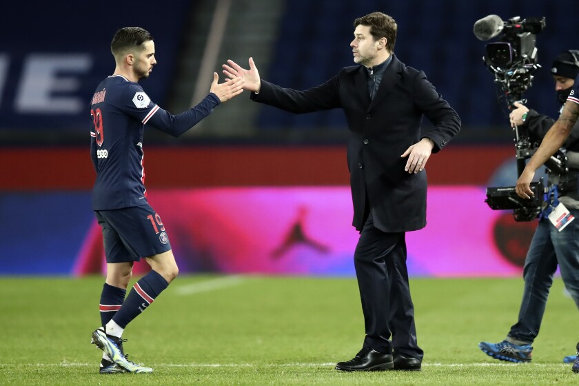 PSG's head coach Mauricio Pochettino, right, congratulates his player Pablo Sarabia after the French League One soccer match between Paris Saint-Germain and Nimes at the Parc des Princes stadium in Paris, France, Wednesday, Feb. 3, 2021. PSG won 3-0. (AP Photo/Michel Euler)