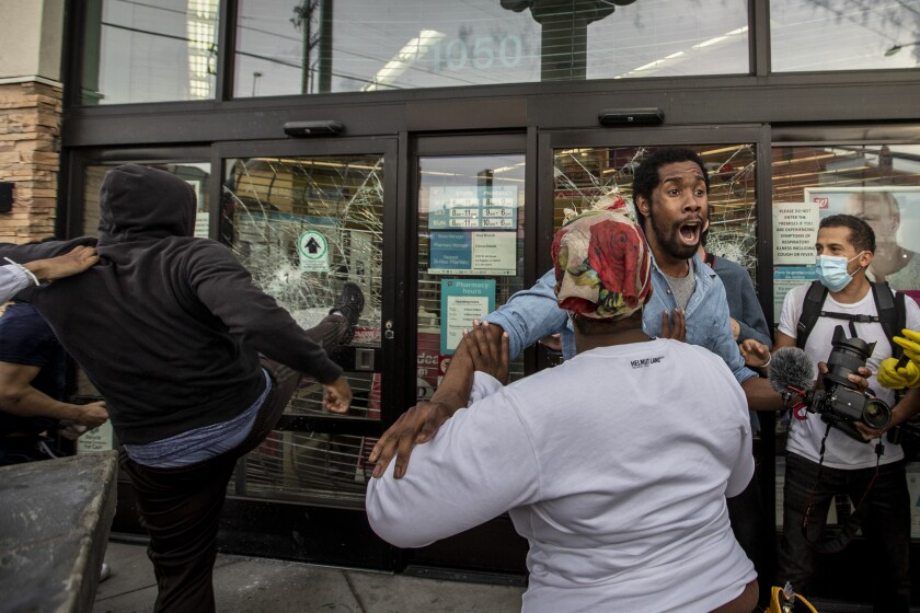 AJ Lovelace tries to stop looters from breaking into a Walgreens store at Santa Monica and Highland.