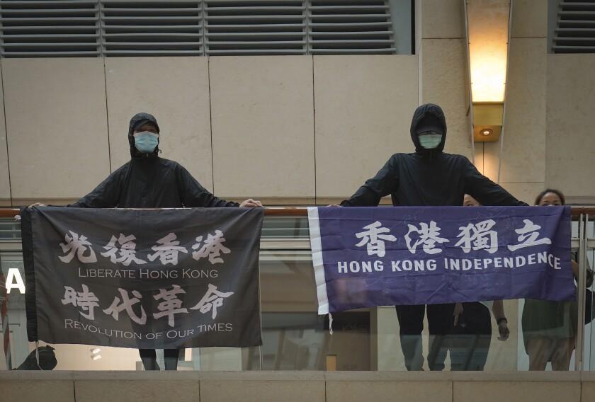 """ARCHIVO - En esta foto del 9 de junio, manifestantes muestran una pancarta que dice """"Liberar a Hong Kong, Revolución de nuestros tiempos"""", izquierda; y otra que dice """"Independencia para Hong Kong"""", en un centro comercial durante una protesta en la ciudad. La policía en Hong Kong arrestó a un hombre de 40 años por sospechas de usar palabras sediciosas luego de que una pancarta de protesta fue vista colgada de su apartamento, dijeron las autoridades el 22 de junio. (AP Foto/Vincent Yu)"""