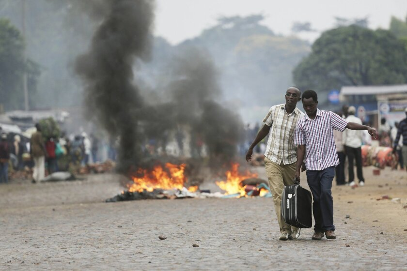 Two men carry a suitcase past a burning barricade in Bujumbura, Burundi Thursday, April 30, 2015, after the government issued and ordered for all university campuses to close down. Bujumbura has been hit by street protests since Sunday as the security forces confront demonstrators who say a third t