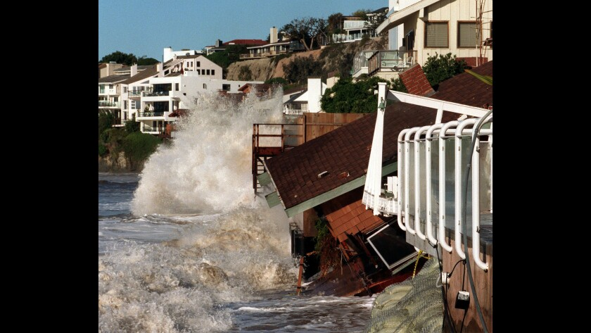 Waves crash into homes along Broad Beach in Malibu .