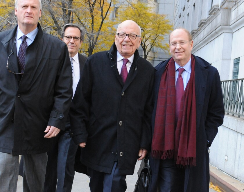 "Rupert Murdoch, center, exits state Supreme Court on Wednesday in New York. Murdoch and his soon-to-be former wife said they were parting with ""mutual respect"" Wednesday after telling a judge they had reached a divorce deal."
