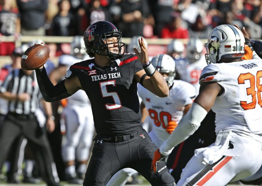 Texas Tech quarterback Patrick Mahomes (5) passes under pressure from Oklahoma State defensive end Emmanuel Ogbah (38) in the second quarter of an NCAA college football game in Lubbock, Texas, Saturday, Oct. 31, 2015. (AP Photo/Sue Ogrocki)