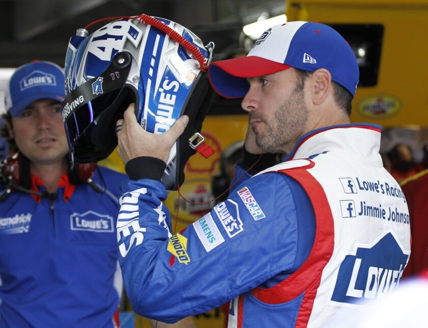 Jimmie Johnson prepares to climb into his car before practice for Sunday's NASCAR Coca-Cola 600 Sprint Cup series auto race at Charlotte Motor Speedway in Concord, N.C., Thursday, May 21, 2015. (AP Photo/Terry Renna)