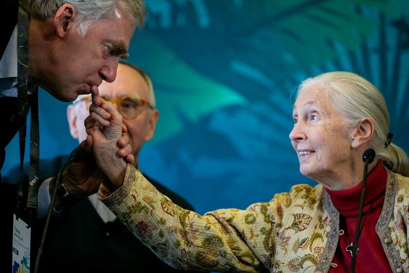 Tracy R. Wolstencroft, president and CEO of the National Geographic Society, kisses the fingernail of Jane Goodall, the famed chimp researcher, before she speaks at a press conference at the Hilton San Diego Bayfront on Tuesday. Goodall spoke alongside Environmental Systems Research Institute (Esri) founder Jack Dangermond and biologist E.O. Wilson.