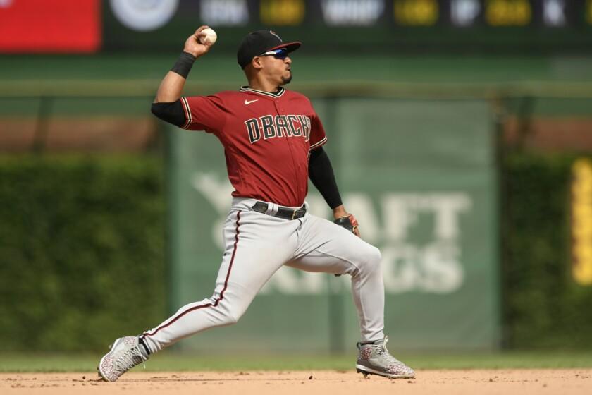 En foto del 25 de julio del 2021, el segunda base de los Diamondbacks de Arizona Eduardo Escobar lanza hacia primera base para el out de Javier Báez de los Cachorros de Chicago. (AP Photo/Paul Beaty)