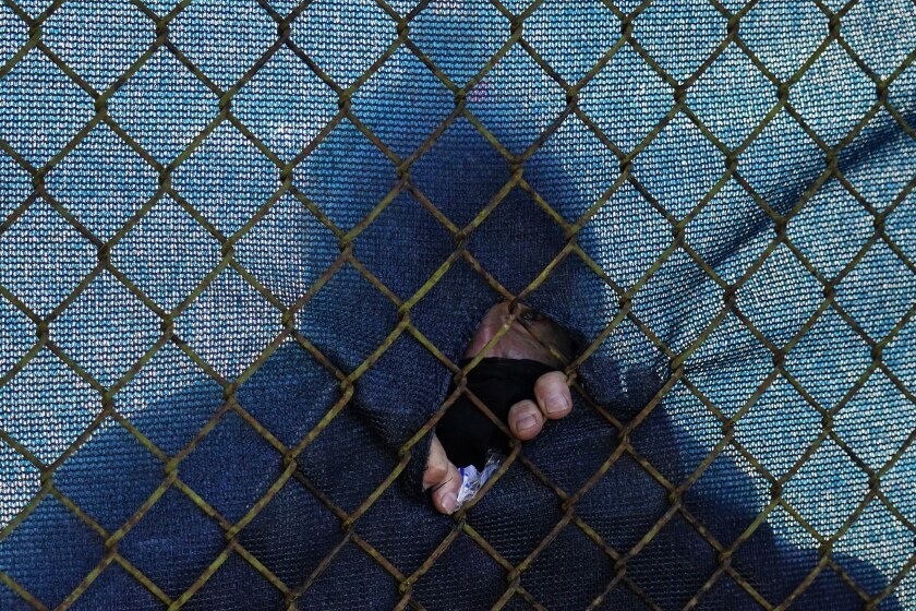 A fans watches through a hole in the fence along the the 12th hole during the first round of the PGA Championship golf tournament at TPC Harding Park Thursday, Aug. 6, 2020, in San Francisco. (AP Photo/Jeff Chiu)