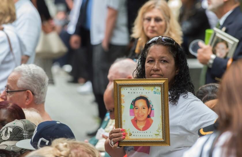 En esta imagen de archivo del 11 de septiembre de 2015, una mujer sostiene una fotografía durante una ceremonia en memoria de los atentados del 11 de septiembre de 2001 contra el World Trade Center en Nueva York. (AP Foto/Bryan R. Smith, Archivo)