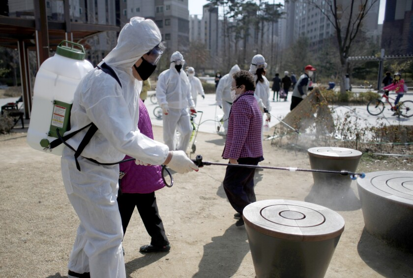 Members of a local residents group wear protective gear as they disinfect a local park as a precaution against the novel coronavirus in Seoul, South Korea.