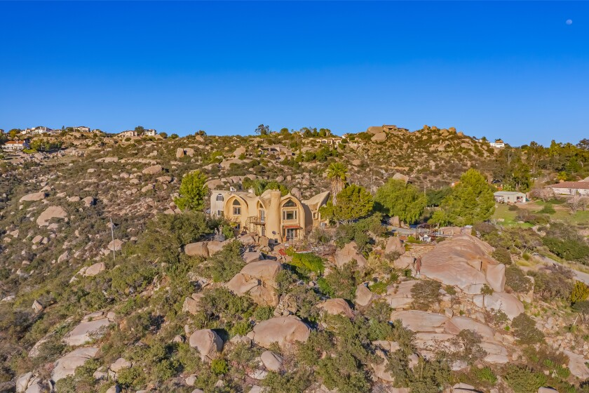 The cave-like abode is built to blend in with the craggy, rock-laden hills that surround it.
