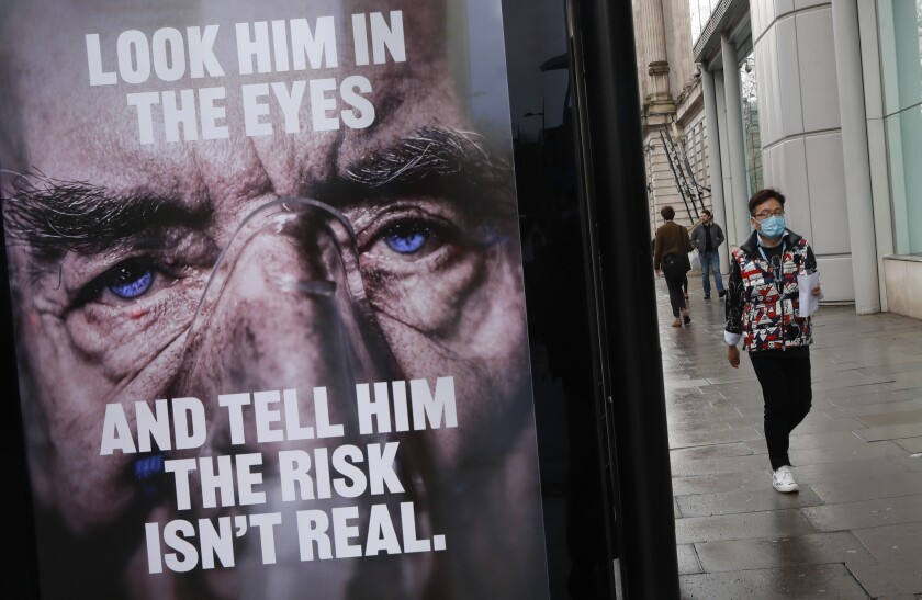 A man wearing a mask against coronavirus walks past an NHS advertisement about COVID-19 in London, Tuesday, Feb. 2, 2021. British health authorities plan to test tens of thousands of people in a handful of areas of England in an attempt to stop a new variant of the coronavirus first identified in South Africa spreading in the community. The Department of Health says a small number of people in England who had not travelled abroad have tested positive for the strain. (AP Photo/Alastair Grant)