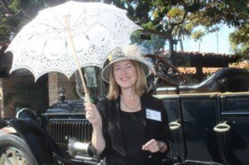Keynote speaker Molly McClain, a history professor at University of san Diego, gives a presentation about Ellen Browning Scripps and gets into the spirit with a vintage umbrella.