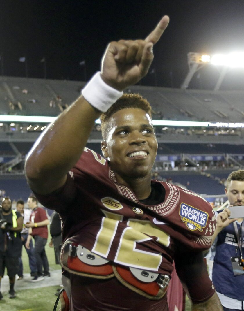 Florida State quarterback Deondre Francois points to cheering fans after defeating Mississippi 45-34 in an NCAA college football game, Tuesday, Sept. 6, 2016, in Orlando, Fla. (AP Photo/John Raoux)