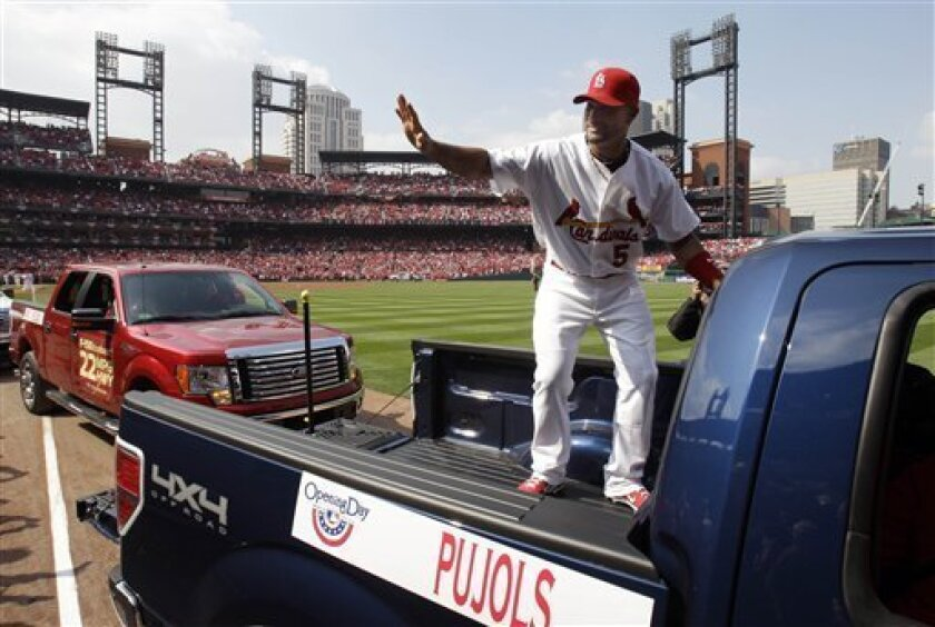 St. Louis Cardinals first baseman Albert Pujols waves to fans as he hops in the back of a pickup to be taken around the field for opening day ceremonies before the start of a baseball game against the San Diego Padres, Thursday, March 31, 2011, in St. Louis. (AP Photo/Jeff Roberson)