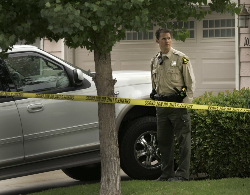 A San Diego County sheriff's deputy stands in front of the home on New Bedford Court in Lakeside where the body of a woman was found dead in a bedroom.