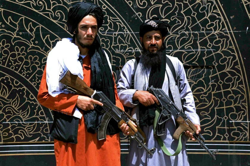 Taliban fighters pose with rifles