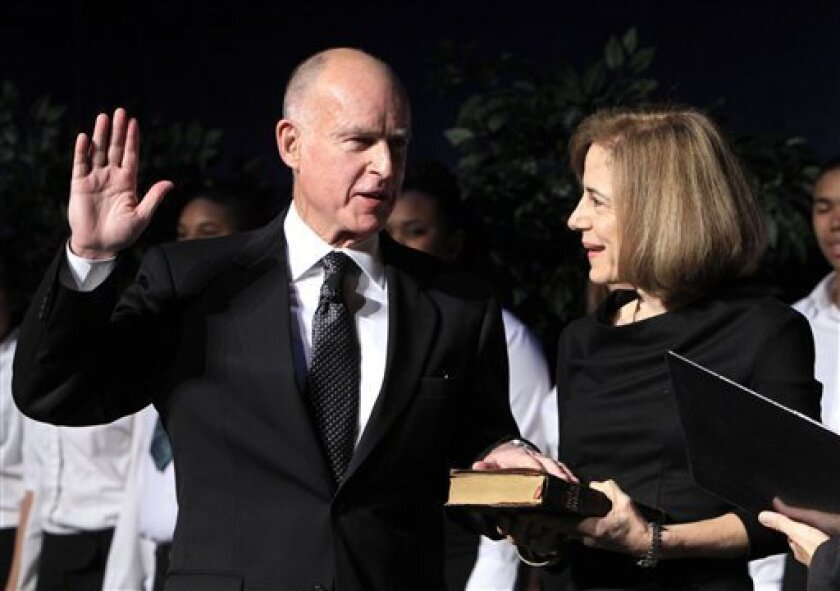 Jerry Brown, left, is sworn-in as the 39th Governor of California as Anne Gust Brown looks on during ceremonies in Sacramento, Calif. Monday, Jan. 3, 2011. (AP Photo/Rich Pedroncelli)