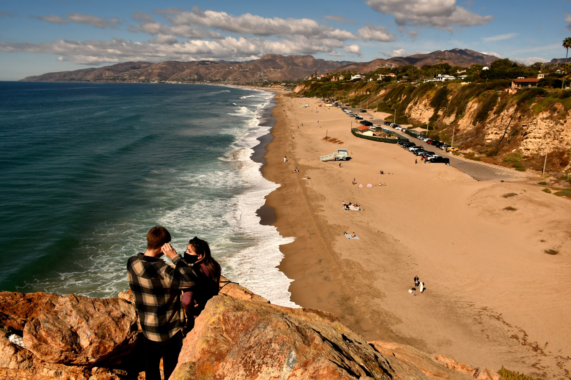 People on a bluff overlooking Point Dume State Beach in Malibu.