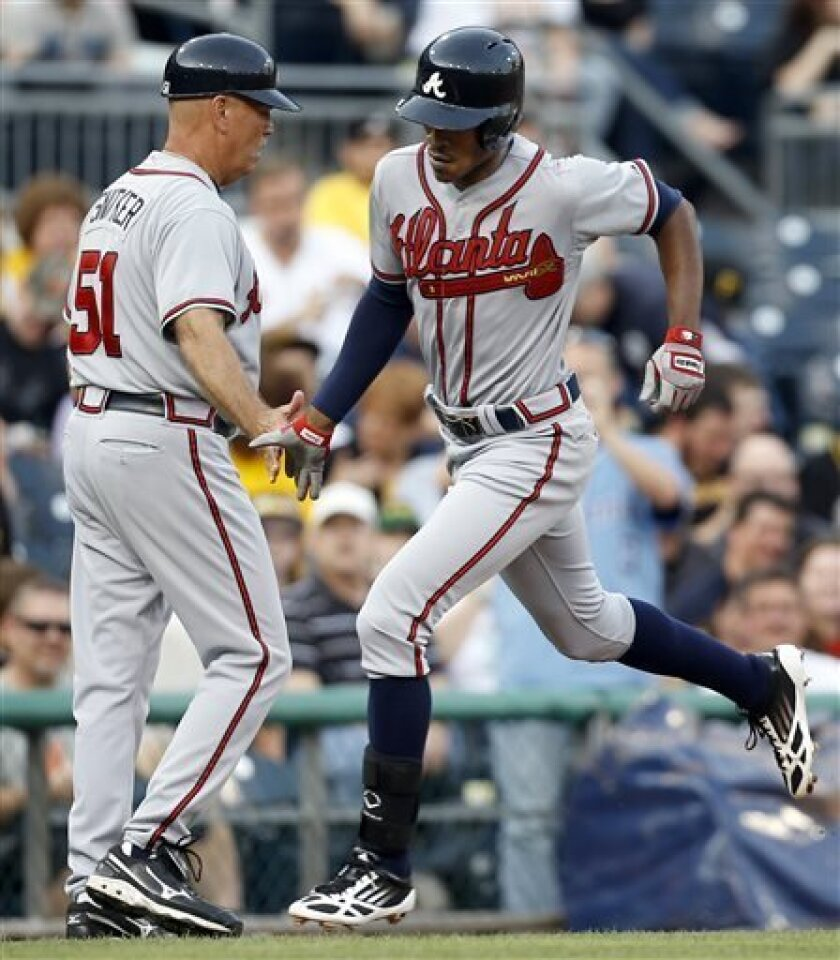 Atlanta Braves' B.J. Upton, right, is greeted by third base coach Brian Snitker after hitting a home run in the first inning of a baseball game against the Pittsburgh Pirates, Thursday, April 18, 2013, in Pittsburgh. (AP Photo/Keith Srakocic)