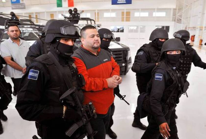 """Teodoro """"El Teo"""" Garcia Simental is held by police in Mexico City in 2012. He had been captured on the roof in his underwear, trying to escape officers."""
