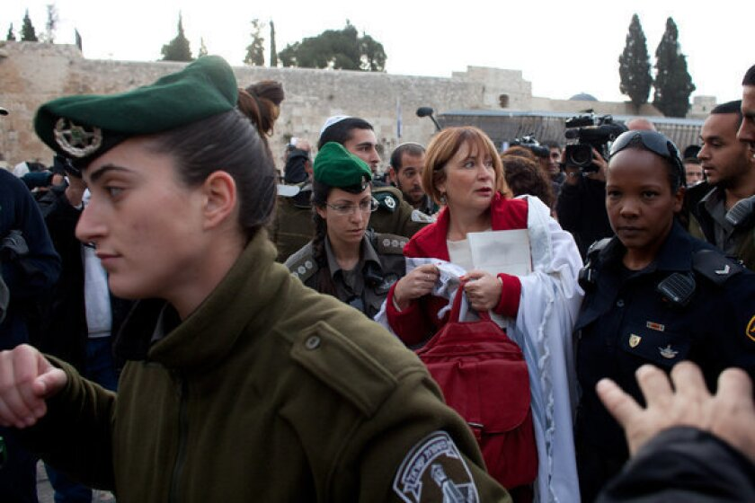 Israeli policewomen detain a member of the religious group Women of the Wall who was wearing a Jewish prayer shawl at the Western Wall.