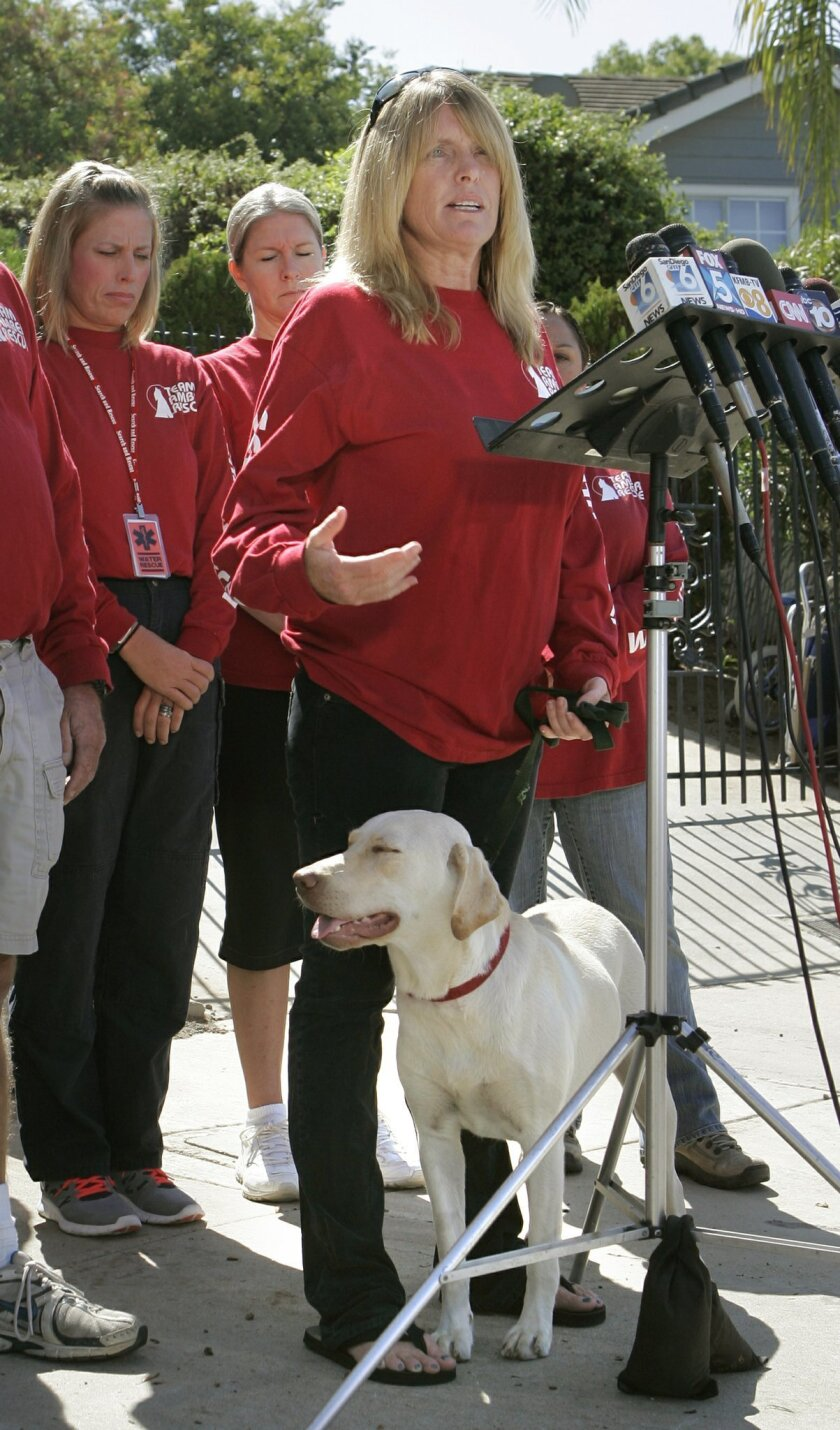 Carrie McGonigle is with her dog Amber at a press conference in front of her house in this 2011 photo.