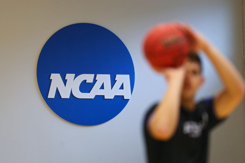 A basketball player shoots in front of the NCAA logo.