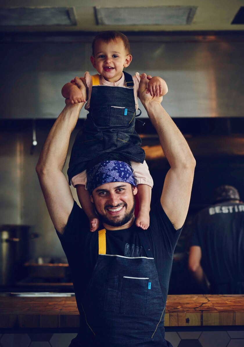 A man holds a young child on his shoulders.