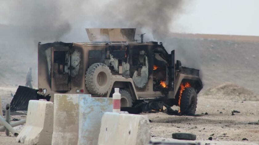 A photo obtained from Hawar News Agency shows a military vehicle at the scene of a suicide car bomb attack on a military convoy in northeastern Syria's Hasakah province. The attack killed five members of a Kurdish-led force accompanying U.S.-led coalition troops.