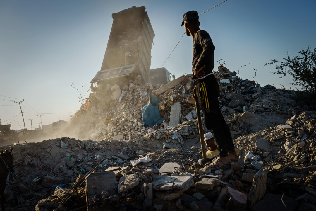 A worker stands in a pile of busted up concrete