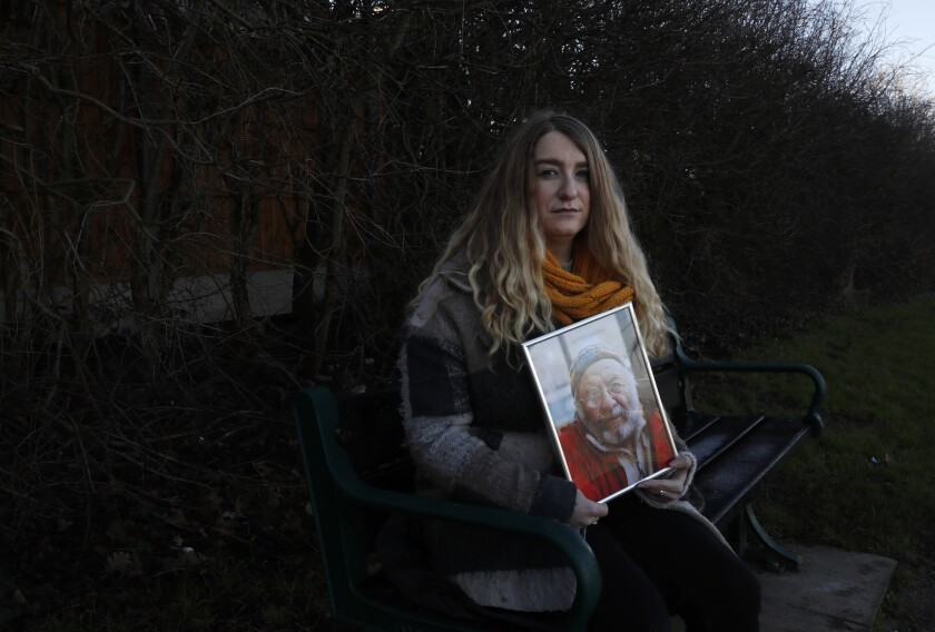 FILE - In this Friday, Jan. 22, 2021 file photo, Jo Goodman, co-founder of the COVID-19 Bereaved Families for Justice group, holds a portrait of her late father Stuart as she poses for a photo in London. Jo's father Stuart died of COVID-19, in April 2020. British Prime Minister Boris Johnson has on Wednesday, May 12 confirmed that an independent public inquiry into the government's handling of the coronavirus pandemic will start hearing evidence next year. While welcoming the announcement, a leading group representing the bereaved think it should begin sooner. (AP Photo/Alastair Grant)