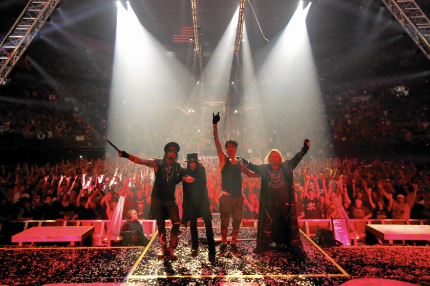 Motley Crue's Nikki Sixx, left, Mick Mars, Tommy Lee and Vince Neil celebrate the ending of another concert as the audience cheers at the Matthew Knight Arena in Eugene, Ore., on July 22, 2015.