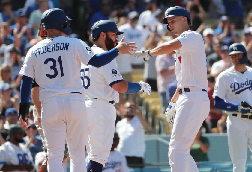 Dodgers shortstop Corey Seager gets high-fives from teammates Joc Pederson (31) and Russell Martin (55)after hitting a three-run home run against the San Francisco Giants on Sunday.