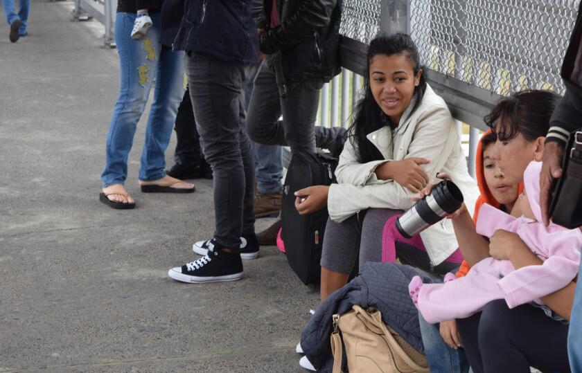 """La cubana Irina Vicardo (d), madre de dos niños de 8 años y 1 año, espera sentada a escasos metros de territorio estadounidense mientras cubanos se manifiestan de forma pacífica formando una fila en la puerta de entrada a Estados Unidos en Laredo (Texas, EE.UU) Los más de cincuenta cubanos varados en la zona de Nuevo Laredo, en la frontera de México con EE.UU., esperan que Donald Trump, que asumirá la Presidencia estadounidense la próxima semana, solucione el conflicto generado por la supresión de la política """"pies secos/pies mojados"""". EFE/Alex Segura Lozano"""
