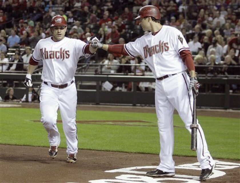 Arizona Diamondbacks' Miguel Montero, left, is congratualted by teammate Kelly Johnson, right, after Montero scored a run on a wild pitch against the Cincinnati Reds in the second inning of a baseball game Friday, April 8, 2011, in Phoenix. (AP Photo/Paul Connors)