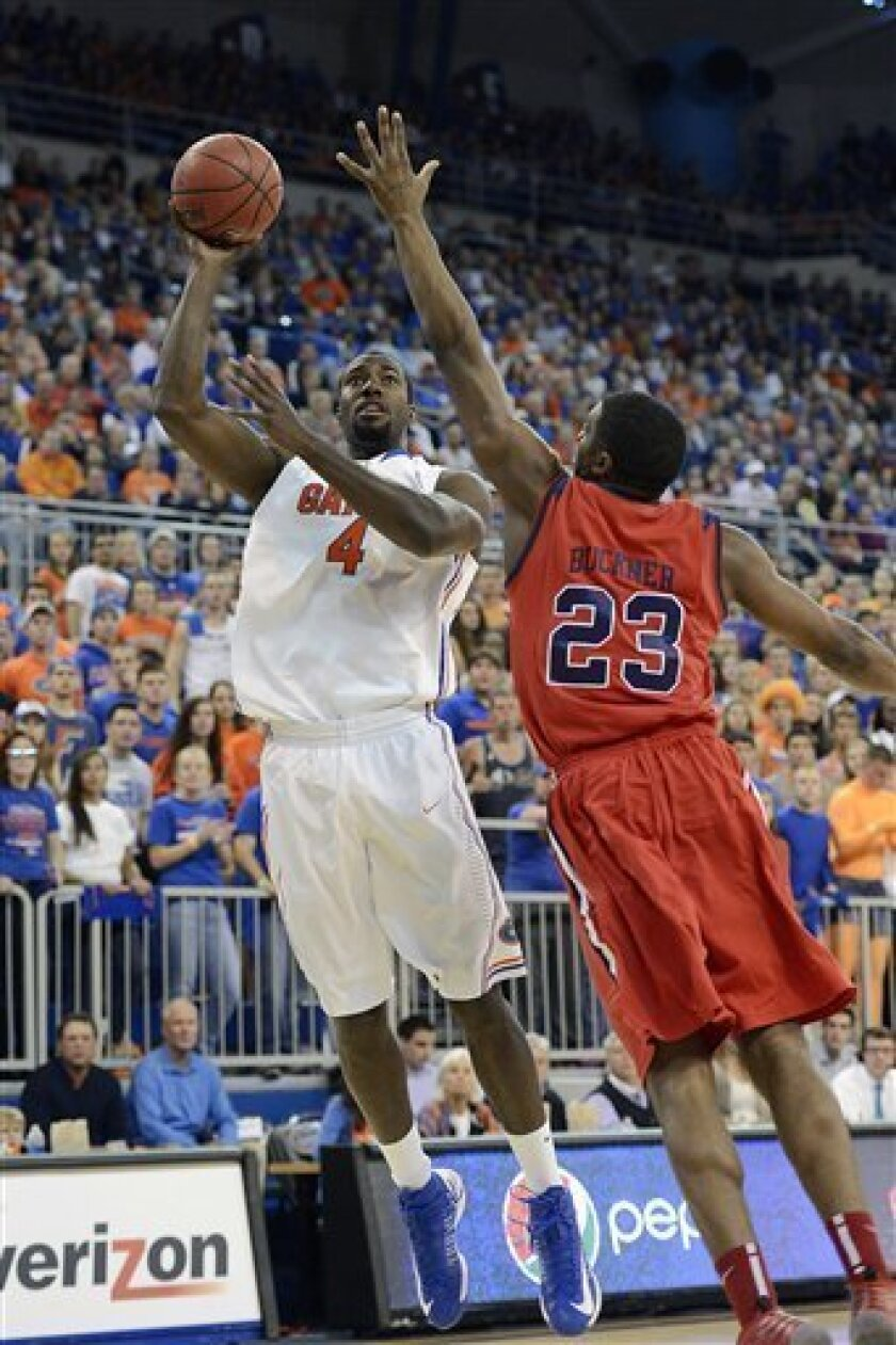 Florida Gators center Patric Young (4) shoots to score as Mississippi forward Reginald Buckner (23) defends during the first half of an NCAA college basketball game in Gainesville, Fla., Saturday, Feb. 2, 2013.  (AP Photo/Phil Sandlin)