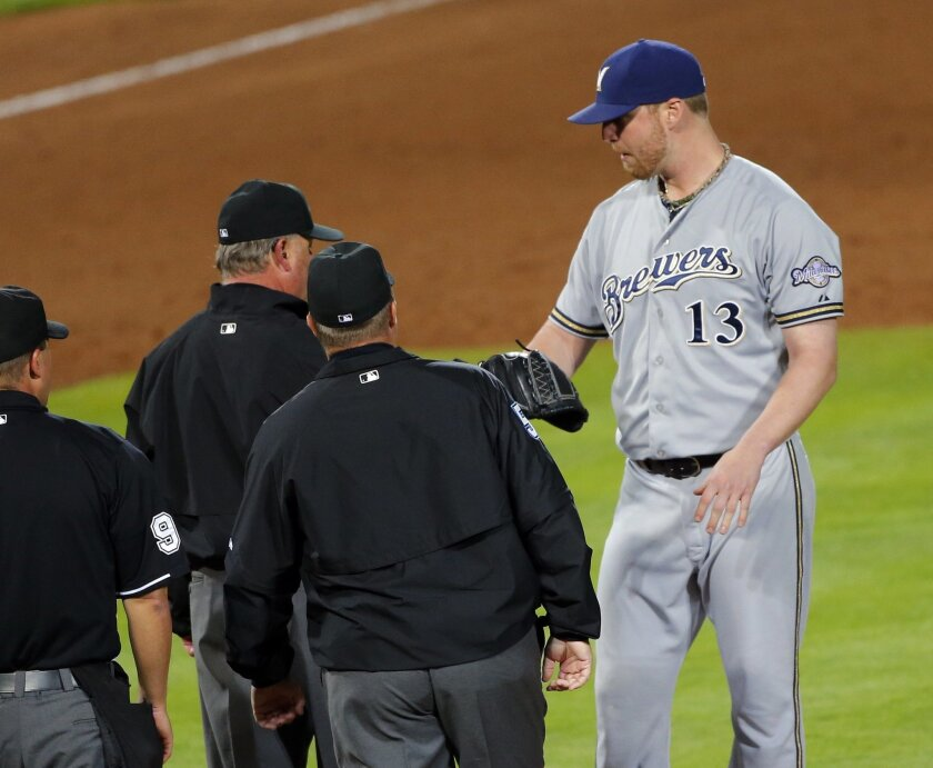 Milwaukee Brewers relief pitcher Will Smith (13) has his glove and arm examined by the umpiring crew before being ejected during the seventh inning of a baseball game against the Atlanta Braves on Thursday, May 21, 2015, in Atlanta. (AP Photo/John Bazemore)