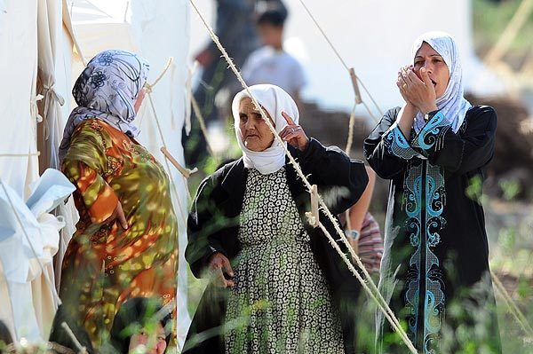 Syrian refugee women chat at the Turkish Red Crescent camp near the Syrian border.