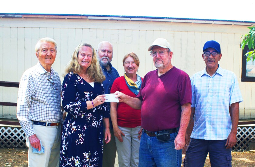 The Community Food Connection President Kim Rearick accepting the $25,000 donation check from Alan Stewart. Joining them for the presentation were board members Marty Judge, Bill Rearick, Ellen Starr and Abraham Saddas.
