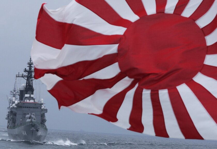 """FILE - In this Sunday, Oct. 14, 2012 file photo, Japan Maritime Self-Defense Force (JMSDF) escort ship """"Kurama,"""" left, navigates behind destroyer """"Yudachi,"""" with a flag, during a fleet review in water off Sagami Bay, south of Tokyo. Japan has released a near-final draft of its first national security strategy that calls for a stronger military amid the rise of China. (AP Photo/Itsuo Inouye, File)"""