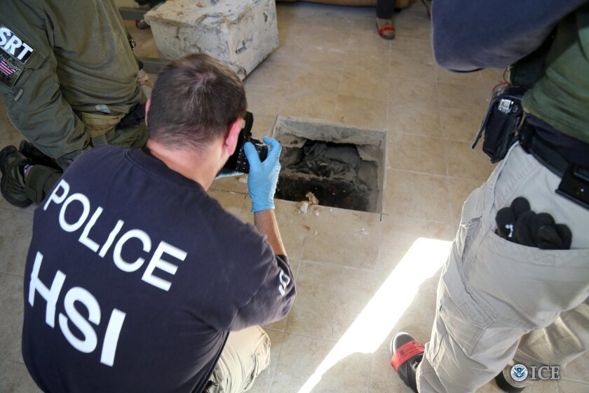 This photo provided by U.S. Immigration and Customs Enforcement shows an investigator Wednesday, March 23, 2016, photographing the terminus of a tunnel at a newly-built home in Calexico, Calif., that runs the length of four football fields to a restaurant in Mexicali, Mexico. An investigation nette